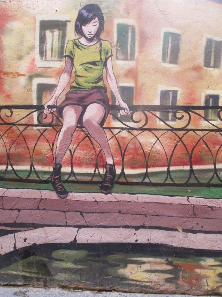 Stree Art a Valencia: i murales e l'arte urbana del Barrio del Carmen - Ragazza seduta su staccionata